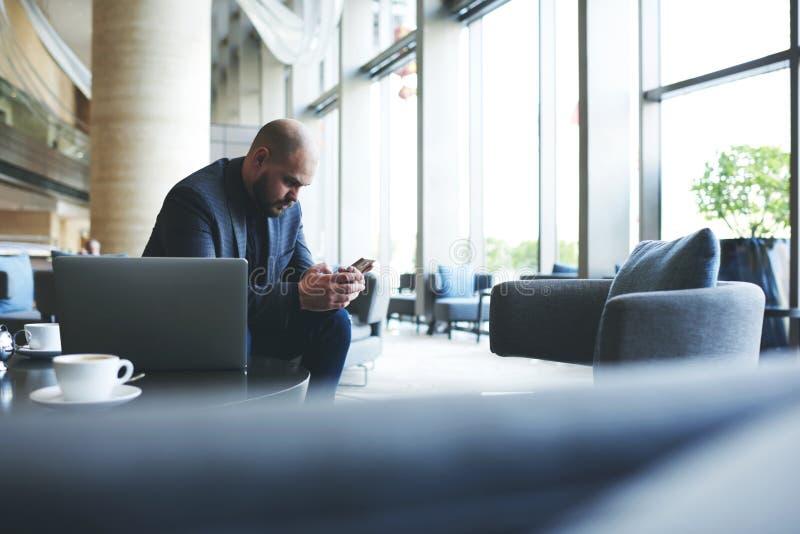De mannelijke ondernemer gebruikt cellphone, terwijl bedrijfslunch in restaurant wacht royalty-vrije stock foto