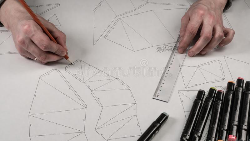 De mannelijke ontwerper maakt een werkende tekening Werkplaats van een stuk speelgoed ontwerper De tellers, de heerser, de pen en royalty-vrije stock foto