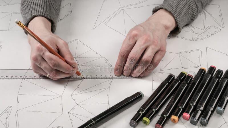 De mannelijke ontwerper maakt een werkende tekening Werkplaats van een stuk speelgoed ontwerper De tellers, de heerser, de pen en stock fotografie