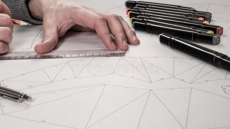 De mannelijke ontwerper maakt een werkende tekening Werkplaats van een stuk speelgoed ontwerper De tellers, de heerser, de pen en royalty-vrije stock afbeelding