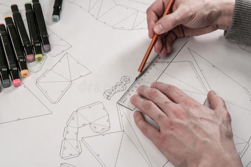 De mannelijke ontwerper maakt een werkende tekening Werkplaats van een stuk speelgoed ontwerper De tellers, de heerser, de pen en stock afbeelding