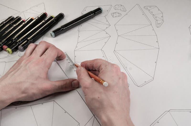 De mannelijke ontwerper maakt een werkende tekening Werkplaats van een stuk speelgoed ontwerper De tellers, de heerser, de pen en royalty-vrije stock foto's