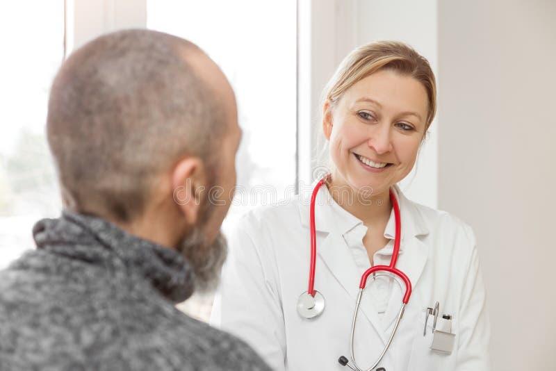 De mannelijke patiënt raadpleegt een vrouwelijke arts stock foto's