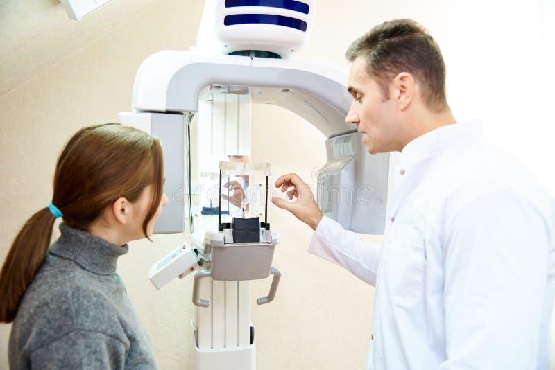 De mannelijke patiënt is in de scanner, en de meisje-arts is dichtbij het controlebord Tandtomografie stock afbeeldingen