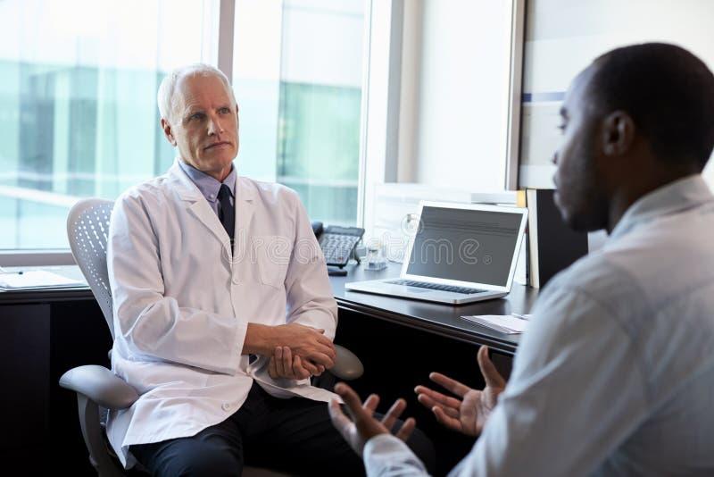 De Mannelijke Patiënt van artsenin consultation with in Bureau stock foto