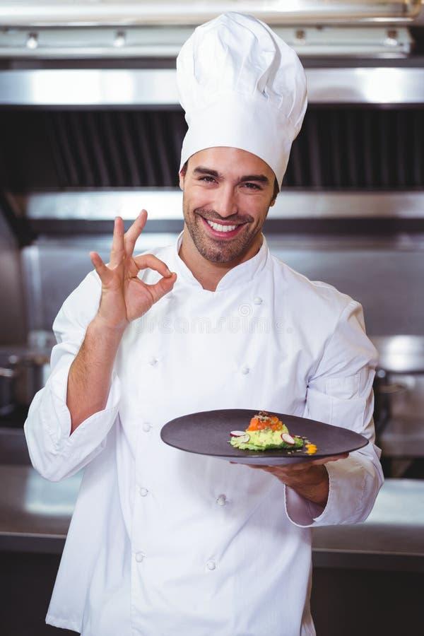 De mannelijke plaat van de chef-kokholding en het doen van o.k. teken royalty-vrije stock afbeelding