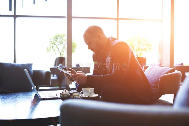 De mannelijke professionele bankier is analyseert munttransacties met digitaal tablet en netto-boek royalty-vrije stock afbeelding