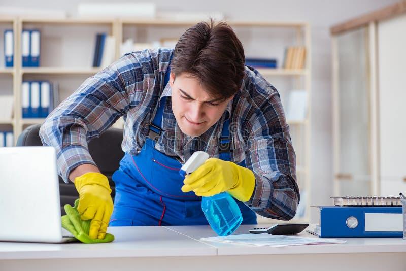 De mannelijke reinigingsmachine die in het bureau werken stock afbeelding