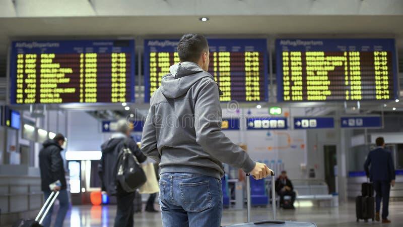 De mannelijke reiziger die vlucht komt en vertrekinformatie bekijken in luchthaven aan stock fotografie
