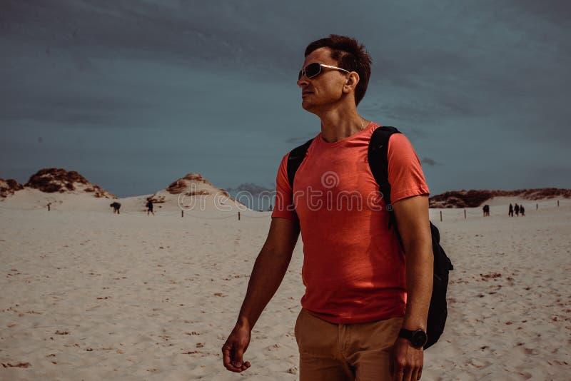 De mannelijke reiziger met rugzak onderzoekt het duin van het poetsmiddelzand dichtbij Gdansk De Kaukasische volwassen alleen rei royalty-vrije stock foto's