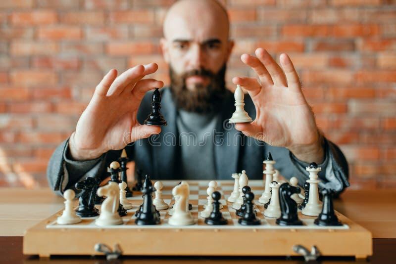 De mannelijke schaakspeler houdt witte en zwarte cijfers royalty-vrije stock afbeelding