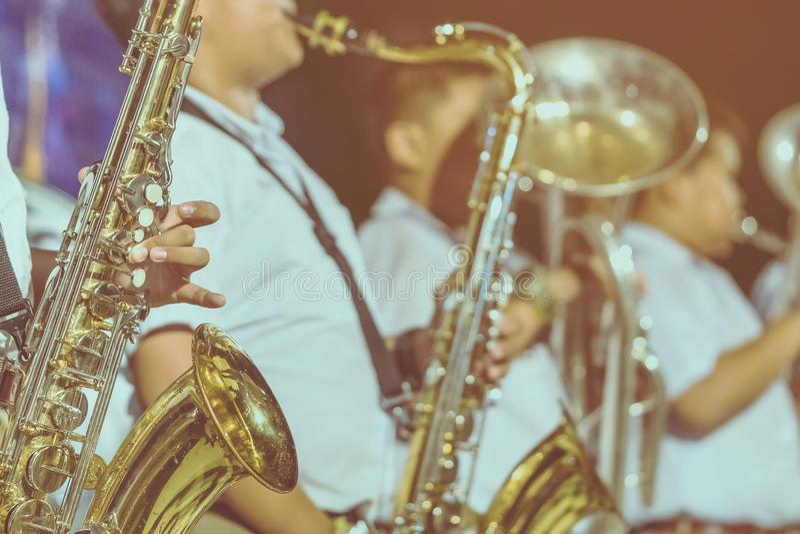 De mannelijke student met vrienden blaast de saxofoon met de band voor prestaties op stadium royalty-vrije stock afbeelding
