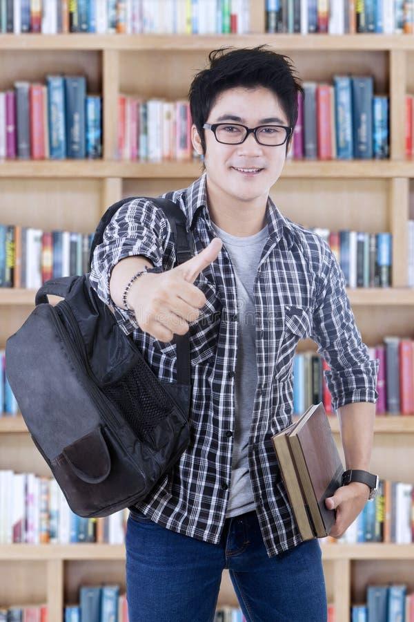 De mannelijke student toont duimen in de bibliotheek stock foto's
