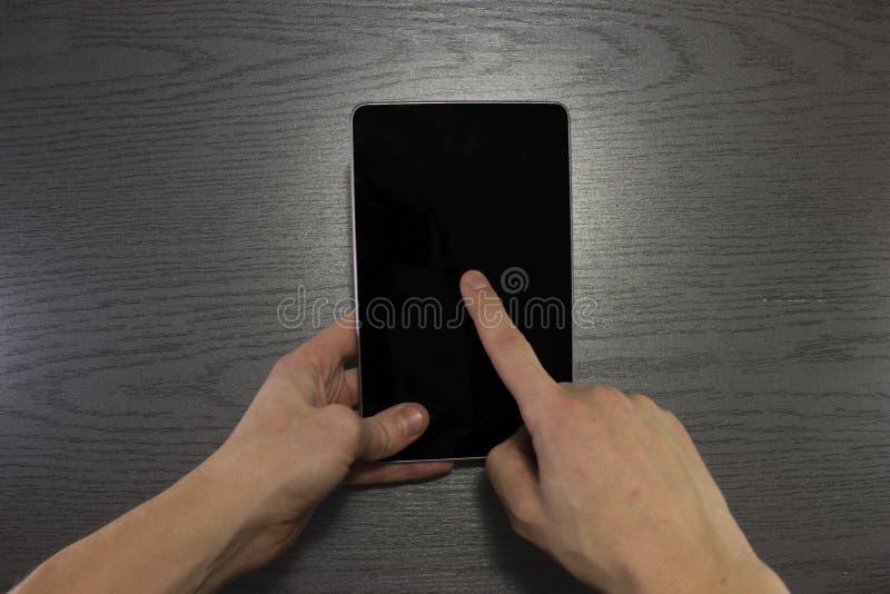 De mannelijke tablet van het handengebruik met het zwarte scherm stock afbeelding