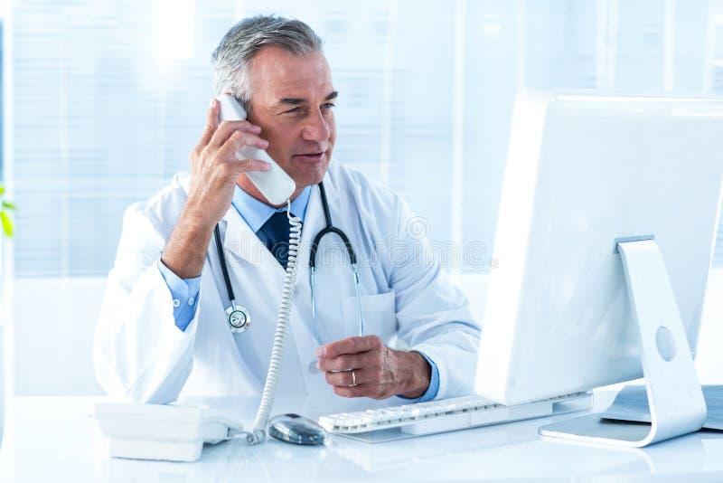 De mannelijke telefoon van de artsenholding terwijl het bekijken computer in het ziekenhuis stock afbeelding