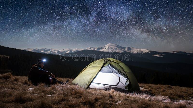 De mannelijke toerist heeft een rust in zijn het kamperen in de bergen bij nacht onder het mooie hoogtepunt van de nachthemel van stock foto's