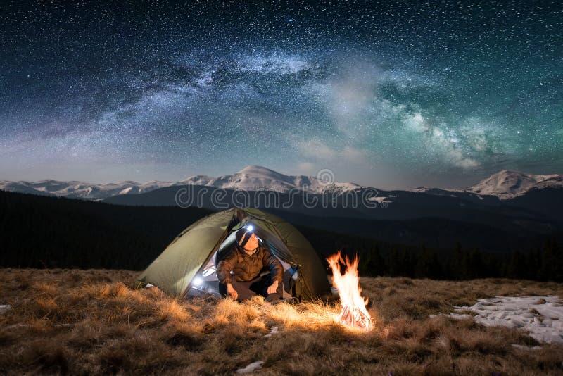 De mannelijke toerist heeft een rust in zijn het kamperen in de bergen bij nacht onder het mooie hoogtepunt van de nachthemel van royalty-vrije stock foto's