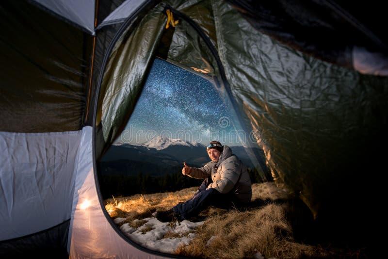 De mannelijke toerist heeft een rust in zijn het kamperen in de bergen bij nacht onder sterrige hemel en melkachtige manier royalty-vrije stock foto's