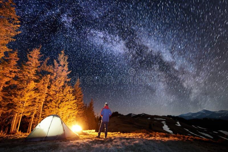 De mannelijke toerist heeft een rust in zijn kamp dichtbij het bos bij nacht onder het mooie hoogtepunt van de nachthemel van ste royalty-vrije stock foto