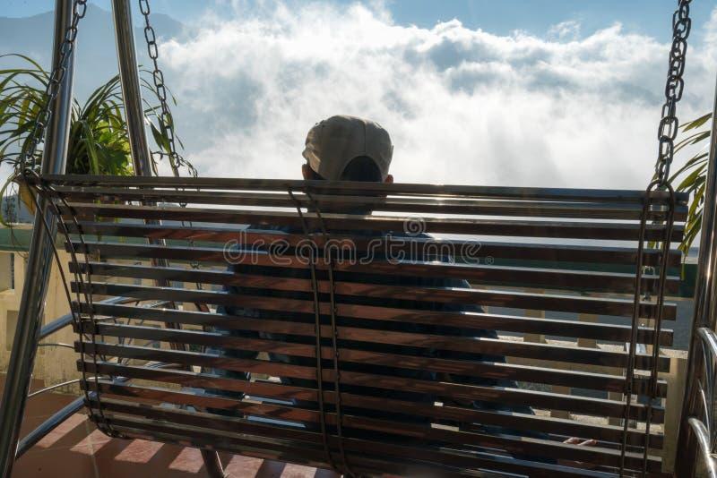 De mannelijke toerist zit op schommeling ziend berglandschap met lage witte wolken onder briljante hemel Ideeën voor reis en het  royalty-vrije stock foto