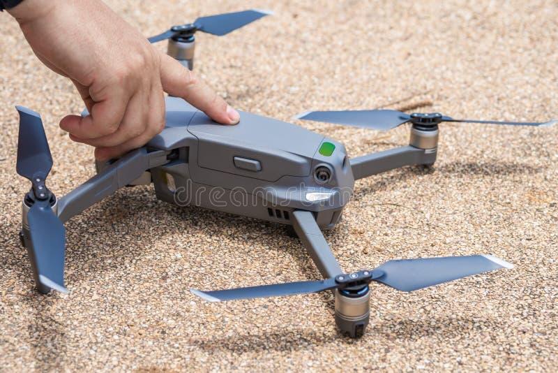 De mannelijke vinger drukt de lanceringsknoop van de hommel voor vlucht, waarmee u foto's en videofilm kunt nemen, dicht royalty-vrije stock fotografie