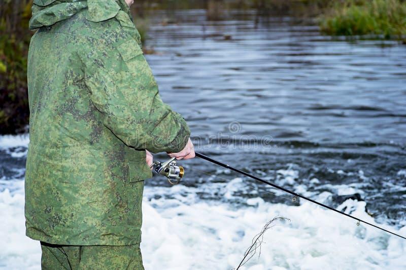 De mannelijke visser vangt op een spinnende spoel de vissen in snel water in buiten het seizoen stock afbeeldingen