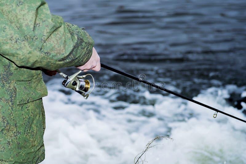 De mannelijke visser vangt op een spinnende spoel de vissen in snel water in buiten het seizoen royalty-vrije stock foto's