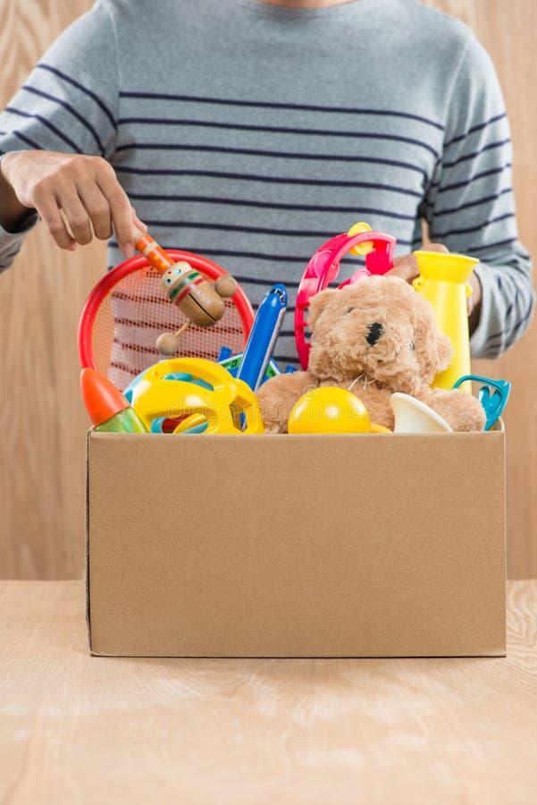 De mannelijke vrijwilligersdoos van de holdingsschenking met oud speelgoed royalty-vrije stock foto