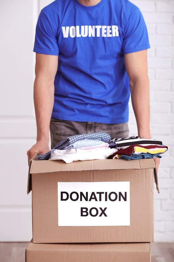 De mannelijke vrijwilligersdoos van de holdingsschenking met kleren royalty-vrije stock foto's