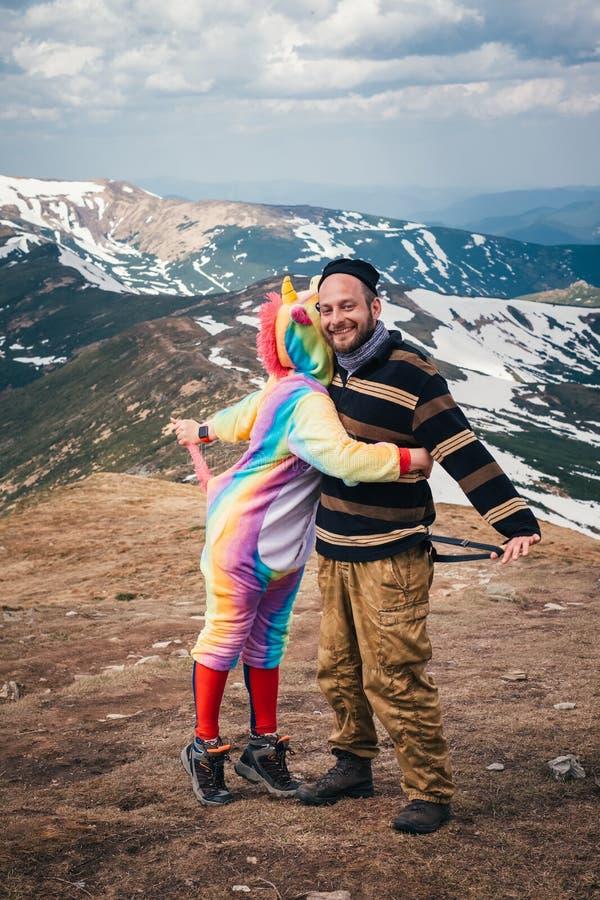 De mannelijke wandelaar ontmoet magische eenhoorn in bergen royalty-vrije stock afbeeldingen