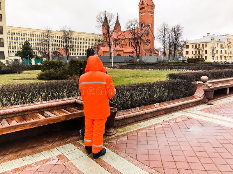 De mannelijke werkende reinigingsmachine in oranje overall die robekleren dragen die maakt de straten van de stad schoon werken stock afbeeldingen