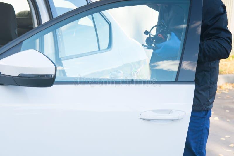 De mannelijke werknemer opende de deur van de auto om de bedrading te bevestigen royalty-vrije stock foto