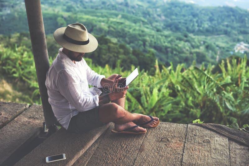 De mannelijke zwerver houdt aanrakingsstootkussen, terwijl in openlucht tijdens zijn reis in Thailand ontspant stock afbeelding