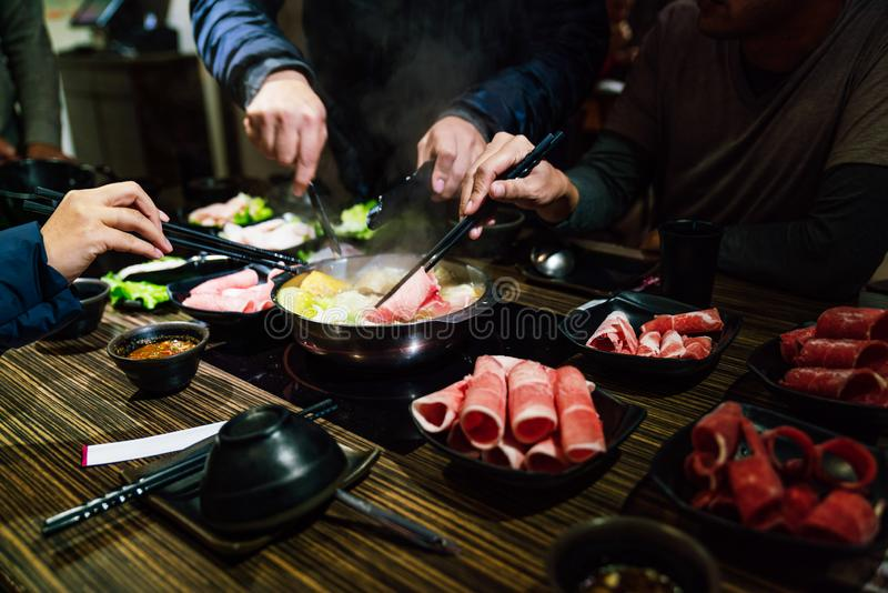 De mannen en de vrouwen overhandigen het knijpend middelgroot zeldzaam rundvlees van plakwagyu A5 en Kurobuta-varkensvlees in het stock foto's