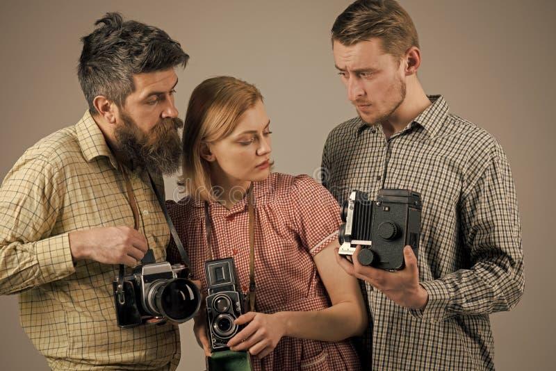 De mannen, vrouw op geconcentreerde gezichten bekijkt camera, grijze achtergrond Bedrijf van bezige fotografen met oude camera's stock fotografie