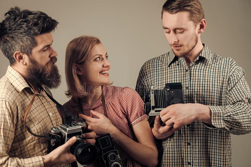 De mannen, vrouw op het glimlachen gezichten bekijkt camera, grijze achtergrond Mensen in geruite kleren, retro stijl Bedrijf van stock foto