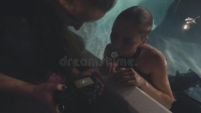 De mannequin die van de vrouwenfotograaf samen foto na zitting onderwater in zwembad kijken stock foto