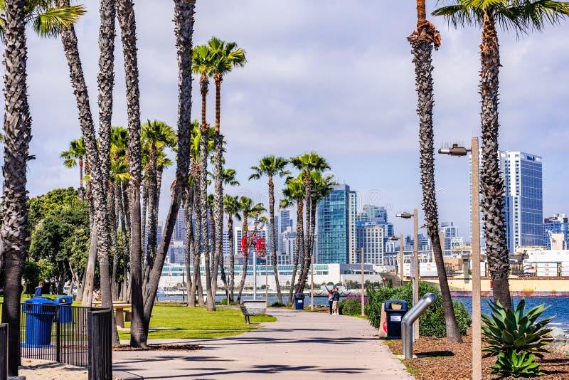 19 de março de 2019 San Diego/CA/EUA - aleia pavimentada alinhada com as palmeiras na ilha de Coronado; A baixa de San Diego visí imagem de stock royalty free
