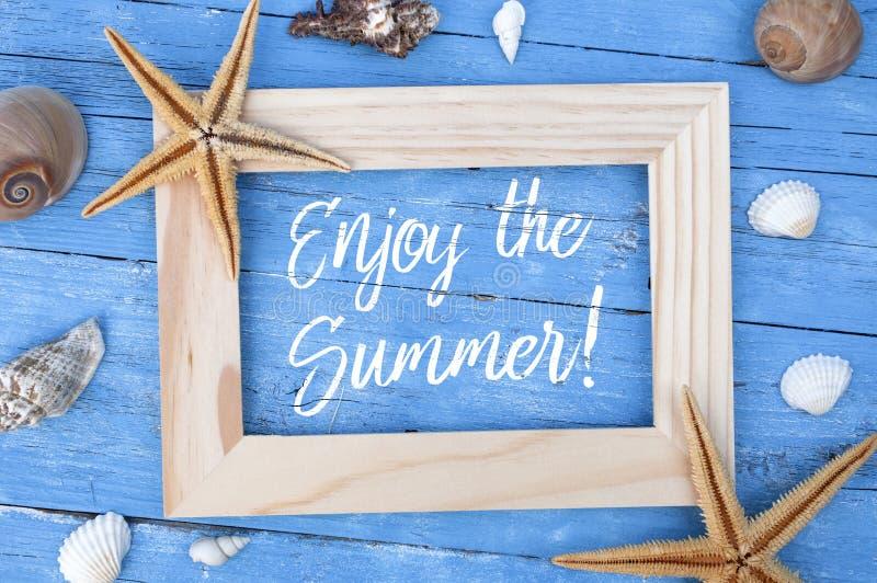 De maritieme decoratie met stervissen, shells op blauw doorstaan hout met slogan geniet van summe stock foto's