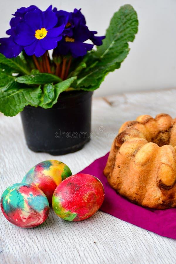 De marmeren cake van Bundtpasen, paaseieren en Sleutelbloem - vulgaris Primula stock afbeelding