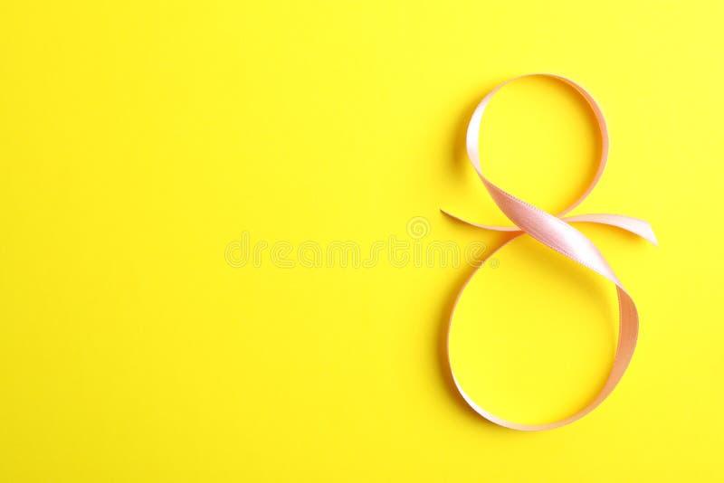 8 de marzo, día internacional del ` s de las mujeres Cuadro ocho de la cinta rosada en fondo amarillo imagen de archivo