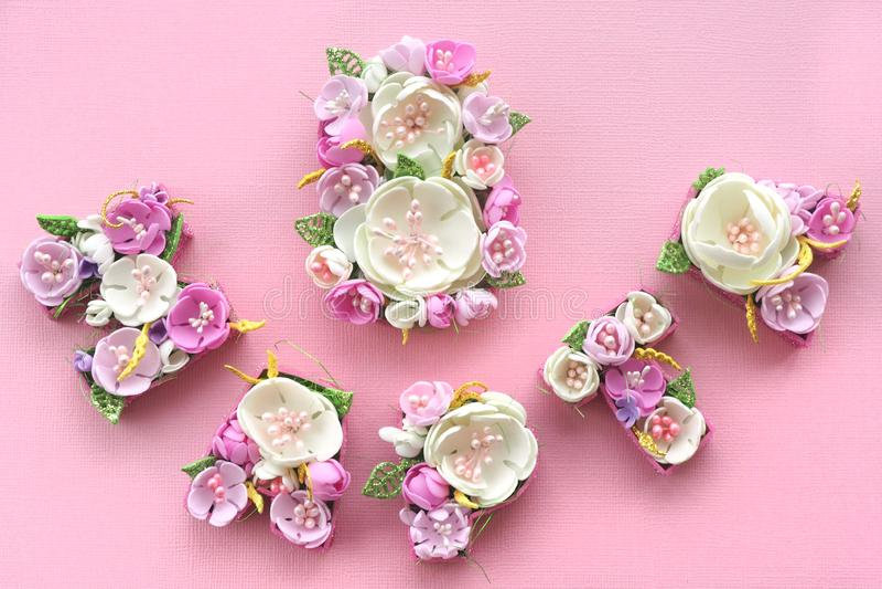 8 de marzo inscripción alineada con las flores en colores pastel multicoloras en las letras rusas en un fondo rosado imagenes de archivo
