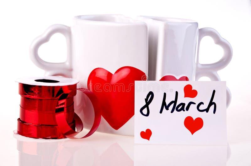 8 de marzo. Las tazas de café en dimensión de una variable de oyen imagenes de archivo