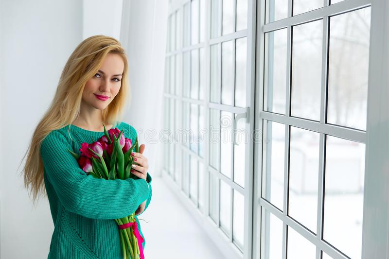 8 de marzo, mujer hermosa joven con los tulipanes fotografía de archivo libre de regalías