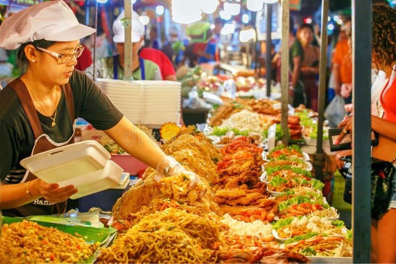 12 de marzo de 2019 Phuket Tailandia Venta asiática tradicional del mercado la mujer commercializa algunos tallarines, carne y ve imagen de archivo