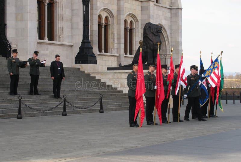 3 DE MARZO DE 2016: Soldados con las banderas que ensayan para la ceremonia del día nacional fuera del edificio del parlamento imagen de archivo