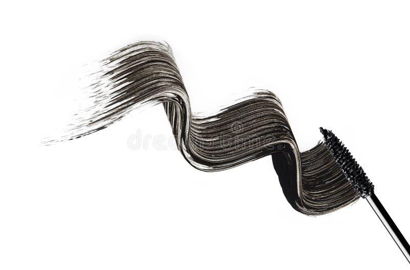 De mascaraborstel schildert golven op een witte oppervlakte royalty-vrije stock afbeeldingen