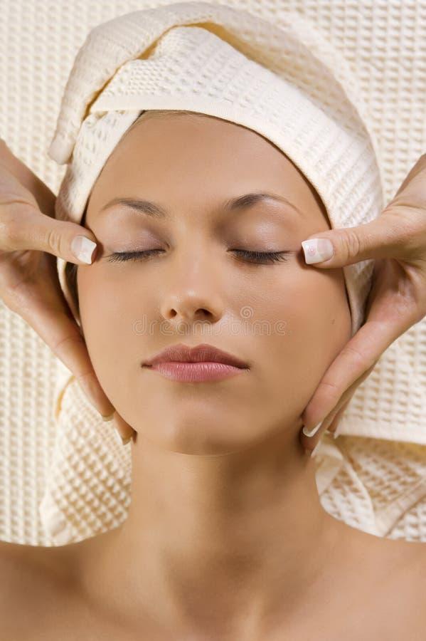 De massage van handen op hoofdtempel stock afbeeldingen