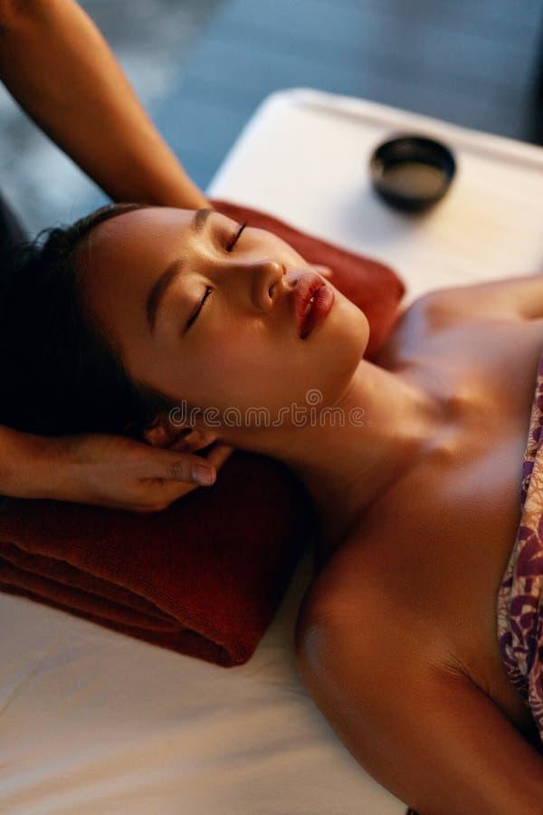 De Massage van het kuuroord Handen die Vrouwenhoofd masseren bij Thaise Schoonheidssalon stock foto