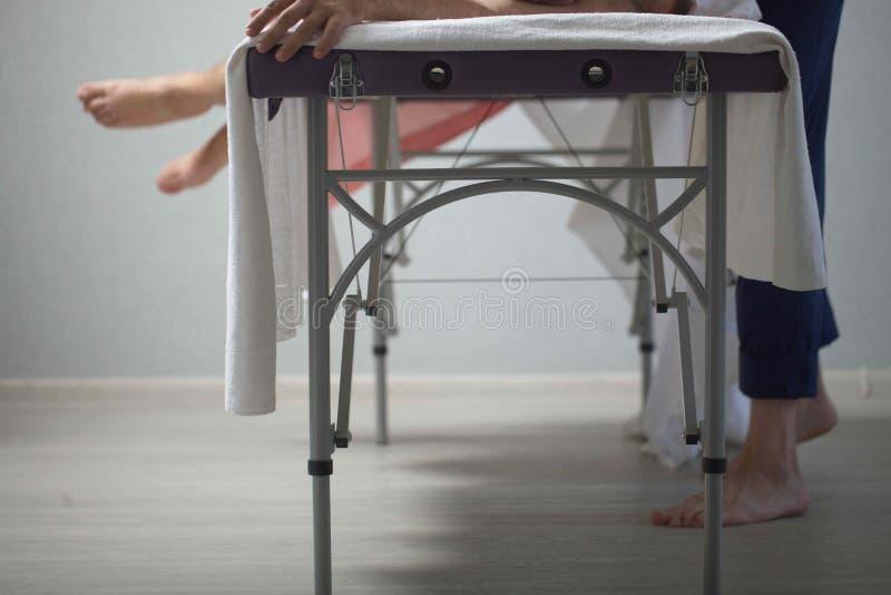 De massagetherapeut maakt een mens tot een massage royalty-vrije stock afbeelding
